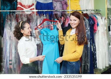 Two women chooses evening gown at clothing store - stock photo