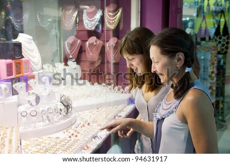 Two women chooses jewelry at shop - stock photo