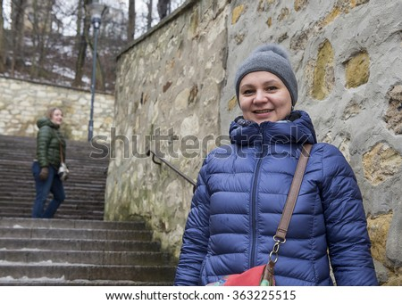 Two women climb the stairs in the autumn park - stock photo