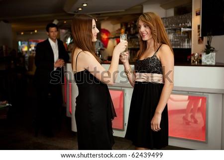 Two women clinking glasses. Focus on women on the left side - stock photo
