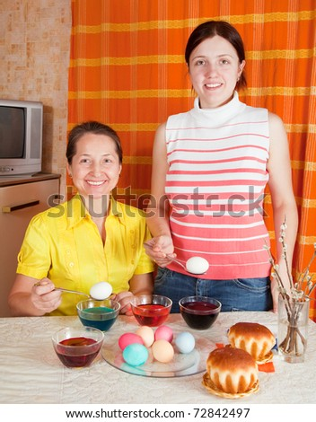 Two women coloring easter eggs in kitchen - stock photo