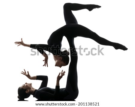 two women contortionist practicing gymnastic yoga in silhouette on white background - stock photo