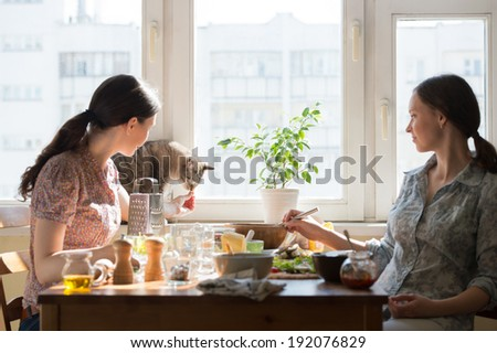 Two women cooking pizza at home. Filling pizza with ingredients and feeding cute cat - stock photo