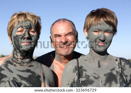 Two women covered mud and man on the sky background - stock photo