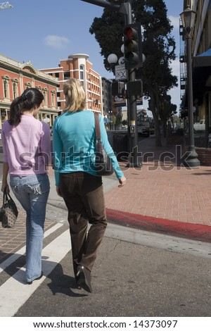 Two women crossing a city street - stock photo