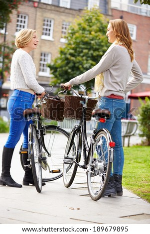 Two Women Cycling Through Urban Park Together