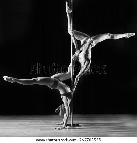 Two women dancing on pylon  - stock photo