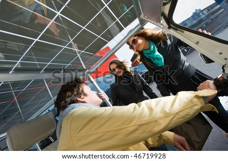 Two women discussing a fare in a solar powered tuc tuc - stock photo