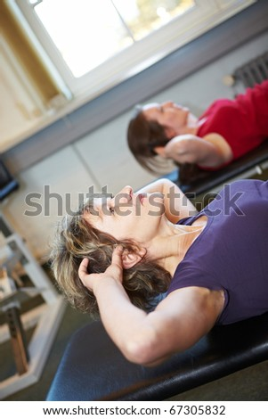 Two women doing crunches in a gym - stock photo