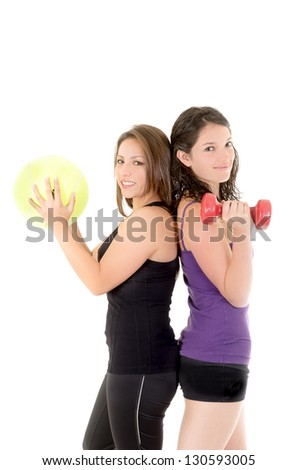Two women doing exercises with barbell and ball isolated on white background - stock photo