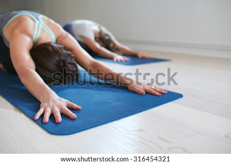 Two women doing stretching workout on fitness mat. Females performing yoga on exercise mat at gym. Child Pose, Balasana. - stock photo