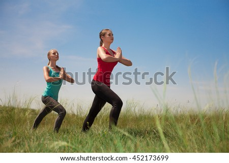 Two women doing yoga outdoors on blue sky background posing on green grass