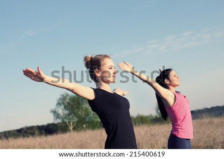 Two women doing yoga outdoors. yoga instructor shows poses - stock photo