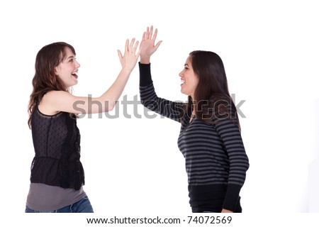Two women, dressed casually, slapping their hands together in a congratulatory manner - stock photo