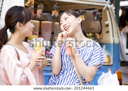 Two women drinking beverages