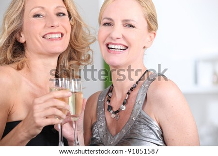 two women drinking champagne - stock photo