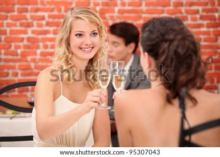 Two women drinking champagne in restaurant - stock photo