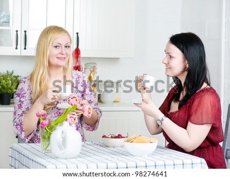 Two women drinking coffee and talking - stock photo