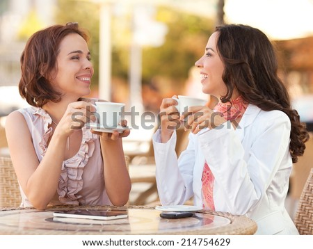 Two women drinking coffee in a city - stock photo