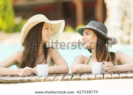 Two women drinking coffee in the pool