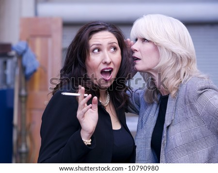 Two women engaging in gossip during a smoking break - stock photo