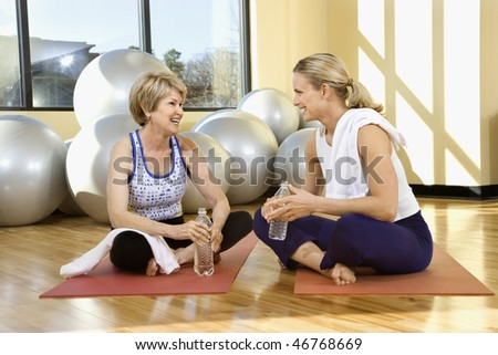 Two women enjoy a conversation while sitting on a gym floor. They are on exercise mats and balance balls are in the background. Horizontal shot. - stock photo