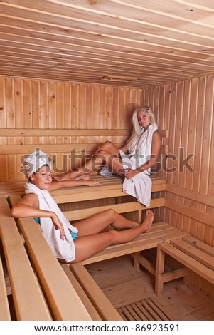 two women enjoying a hot sauna, having a casual chat - stock photo
