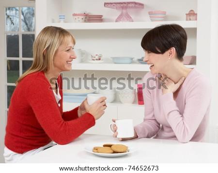 Two Women Enjoying Hot Drink In Kitchen - stock photo