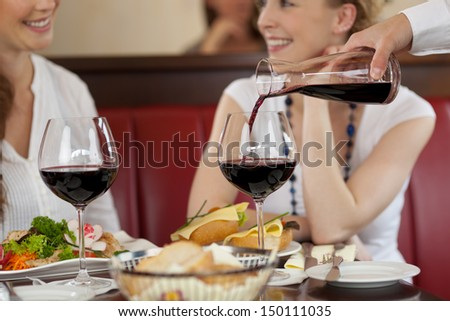 Two women enjoying red wine sitting eating a meal in a restaurant and chatting while the waiter replenishes their glasses - stock photo
