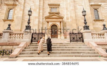 Two women enter into the catholic church - stock photo