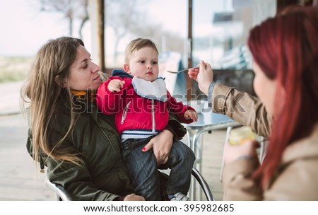 Two women feeding baby food to a toddler outdoors