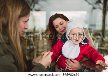 Two women feeding baby food to a toddler outdoors - stock photo
