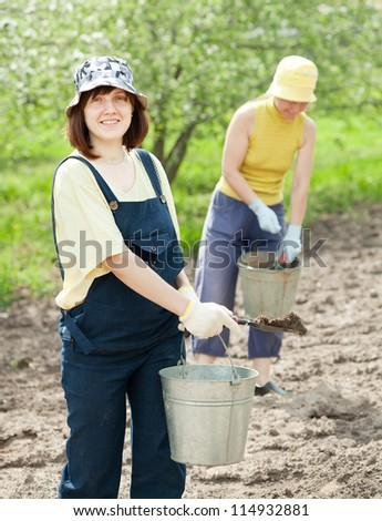 Two women fertilizes the soil in garden - stock photo