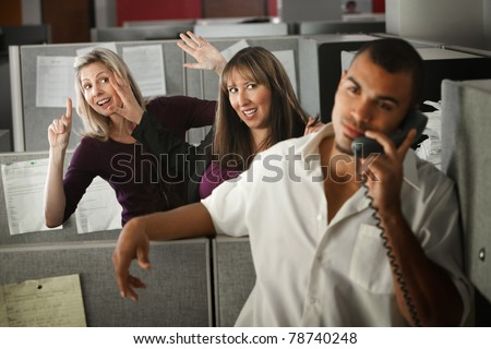 Two women flirting with a male coworker in the office - stock photo