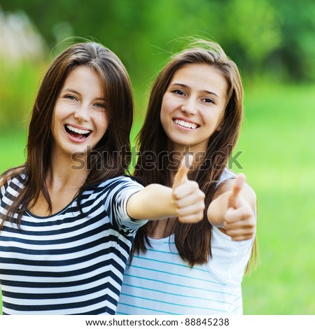 Two women friends beautiful smiles long dark hair standing next hand stretched front - stock photo