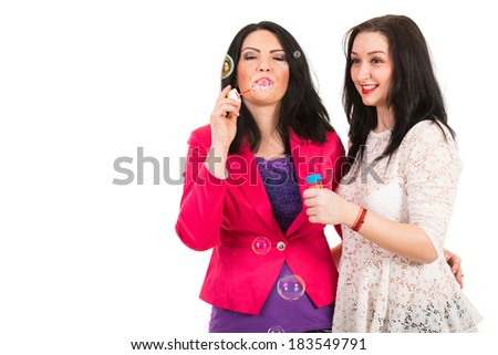 Two women friends blow out soap bubbles and having fun isolated on white background
