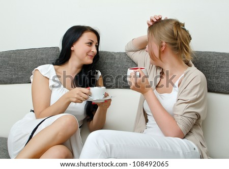 Two women friends chatting over coffee at home - stock photo