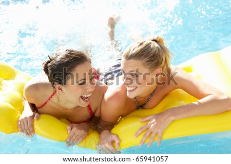 Two women friends having fun together in pool - stock photo