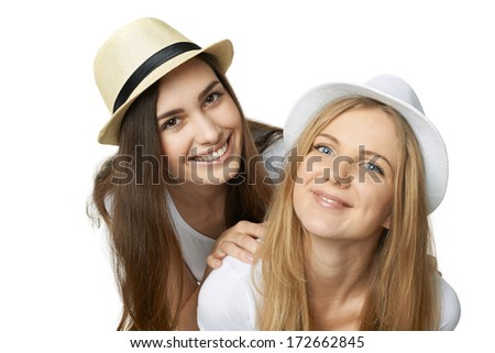 Two women friends having fun. Two happy girls in straw hats and white tshirts hugging and smiling against white background - stock photo