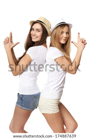 Two women friends having fun. Two happy girls in straw hats and white tshirts making gun shape with hands, against white background - stock photo