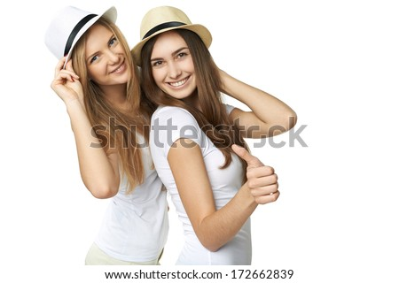Two women friends having fun. Two happy girls in straw hats and white tshirts smiling and showing thumb up gesture against white background - stock photo