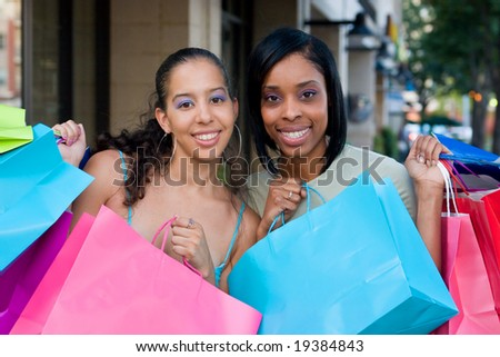Two women friends in the city on a shopping trip carrying colorful shopping bags. - stock photo