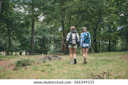 Two women friends with backpacks walking - stock photo