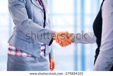 Two women give handshake after agreement - stock photo