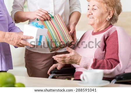 Two women giving the colorful presents to older lady on wheelchair - stock photo