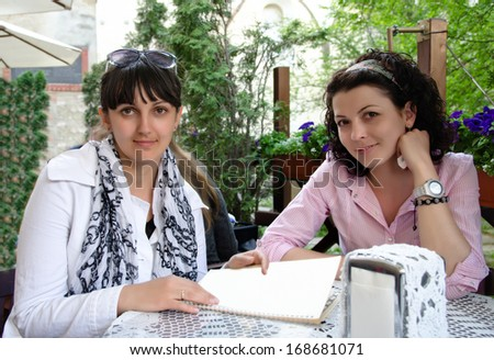 Two women having a meeting outdoors sitting at a table on a leafy green patio discussing paperwork conceptual of a business broker, financial adviser or insurance agent - stock photo