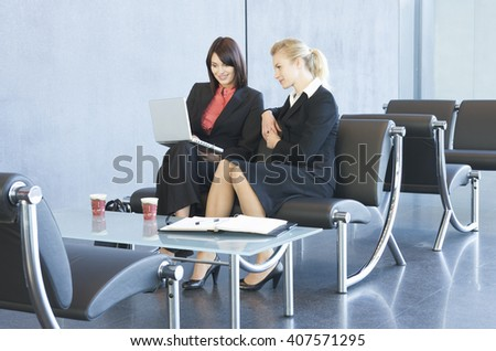 Two women having an informal business meeting, looking at a laptop - stock photo
