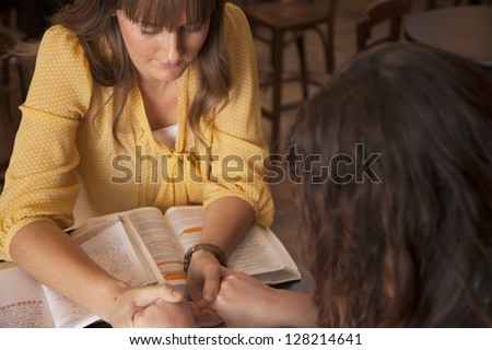 Two women hold hands and pray as they study the bible. - stock photo