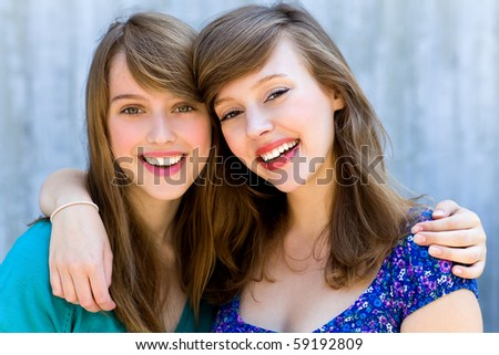 Two women hugging and smiling - stock photo