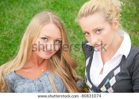 Two women hugging and smiling sitting on the grass at city park